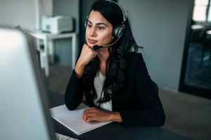 Pensive businesswoman with headset looking at computer screen.